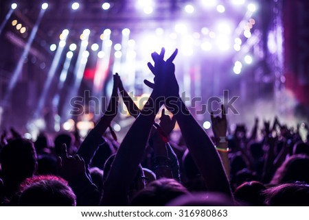 Audience with hands raised at a music festival and lights streaming down from above the stage. Soft focus, blurred movement.  #316980863