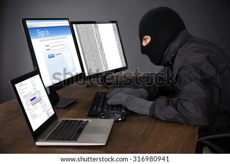 Hacker Wearing Balaclava Hacking Computers At Desk #316980941