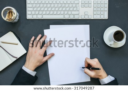 Businessman writing a letter at office working table with notepad, computer and cup of coffee. Top view. #317049287