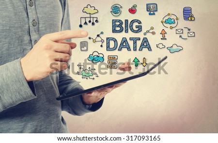 Young man pointing at Big Data concept over a tablet computer Royalty-Free Stock Photo #317093165