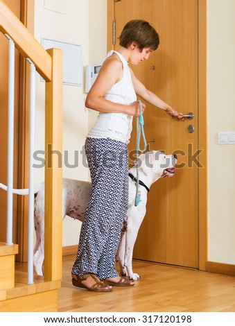 Young woman with white big dog on leash staying at door #317120198