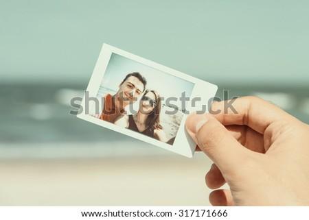 Retro Photo Of Man Hand Holding Instant Photo Of Happy Couple On Beach