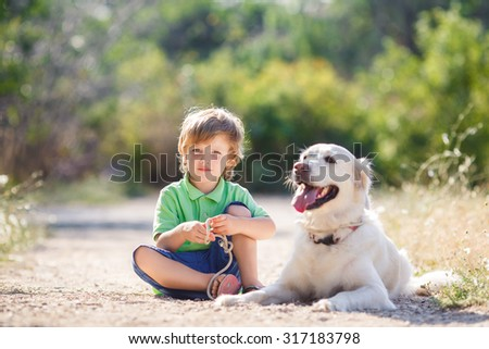 Little boy with a golden retriever dogs outdoor. Boy with a dog on the nature. child with dog outdoor. child and animal #317183798