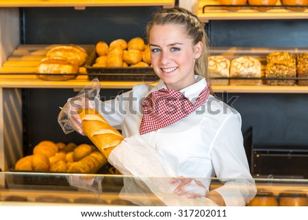 Shopkeeper in bakery putting loaf of bread into paper bag #317202011