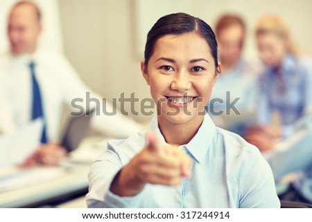 business, people and teamwork concept - smiling businesswoman pointing finger at you with group of businesspeople meeting in office #317244914