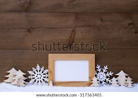 Brown Christmas Card With White Christmas Decoration On Snow. Picture Frame With Copy Space For Advertisement. Snowflakes, Christmas Trees. Rustic Wooden Background