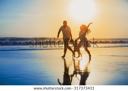 Happy family - father, mother, baby son hold hands and run with fun along edge of sunset sea on black sand beach. Active parents and people outdoor activity on tropical summer vacations with children #317373431