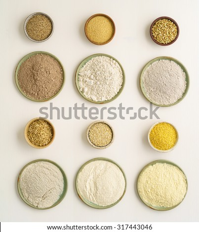 Collection of gluten free grain and flours in small bowls. Top from left teff, amaranth, buckwheat. Bottom from left rise, quinoa, millet #317443046