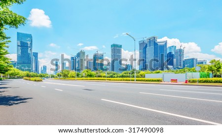 empty street with trees aside and skyscrapers as background #317490098
