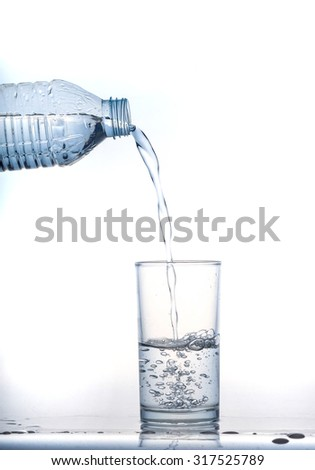 pouring cool water in glass on white background #317525789