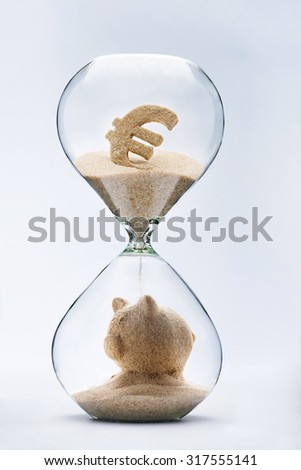 Banking concept. Piggy bank made out of falling sand from euro sign flowing through hourglass #317555141