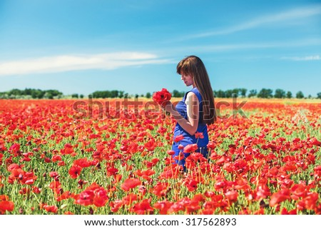 The beautiful girl on a red field with poppies #317562893