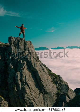 Toned image adult woman with a backpack with arms outstretched stands on the edge of a cliff and looking at the sunrise against the blue sky and thick clouds floating down #317683163