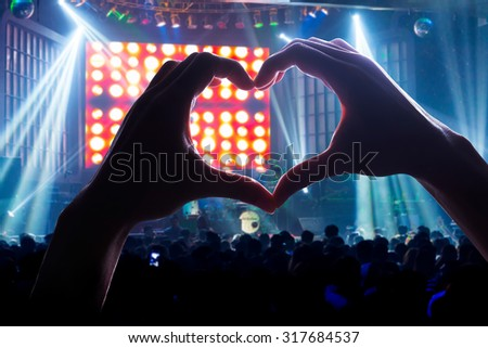 Crowd Audience the power of music, silhouette heart shaped hands shadow Royalty-Free Stock Photo #317684537