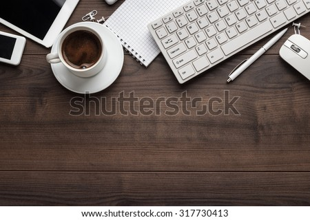 office table with notebook, computer keyboard, mouse, cup of coffee, tablet pc and smartphone. copy space #317730413