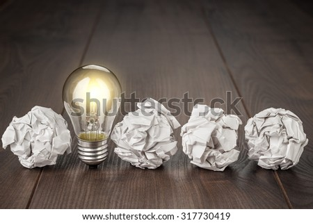great idea concept with crumpled office paper and light bulb standing on the table #317730419