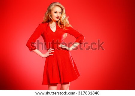 Charming smiling young woman in red dress and with blonde curled hair. Beauty, fashion. Cosmetics, make-up. Red background. #317831840