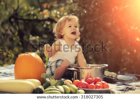 One smiling boy at picnic sitting with ladle pot orange pumpkin red tomato squash and cucumber playing with food sitting on blue checkered plaid on natural background sunny day, horizontal picture