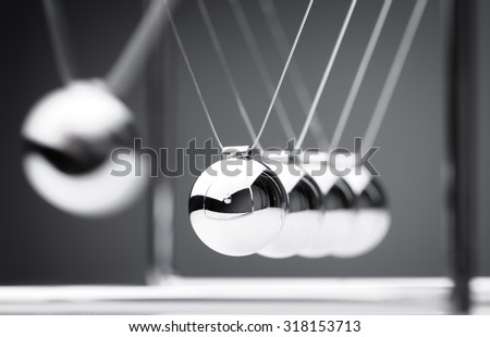 Newton's cradle physics concept for action and reaction or cause and effect Royalty-Free Stock Photo #318153713