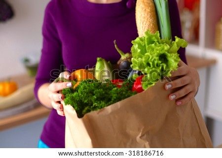 Healthy positive happy woman holding a paper shopping bag full of fruit and vegetables #318186716