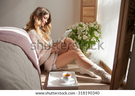 Beautiful Woman Morning, Sitting on the Floor near the Bed, Open Window, side view. Attractive Model Enjoys  Cup Coffee Before Work and Reads News. Woman is Reading, Sun was shining into the Room
