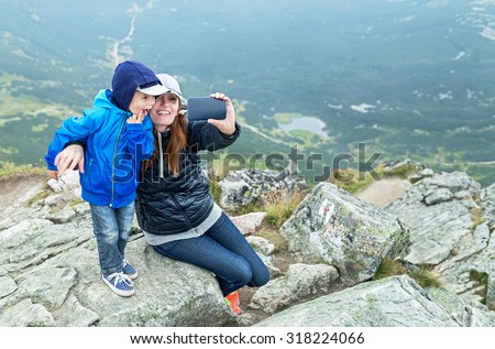 Taking selfie! Happy mother and baby boy making self portrait in the mountains. Woman holding smartphone camera to take picture. Kasprowy Wierch (peak). Poland. Travel, technology concept. Copy space.