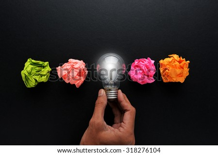 new idea concept with crumpled office paper, male hand holding light bulb #318276104