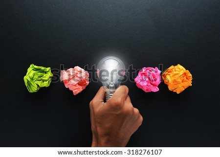 new idea concept with crumpled office paper, male hand holding light bulb #318276107