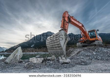 big orange digger on gravel heap with big shovel Royalty-Free Stock Photo #318350696