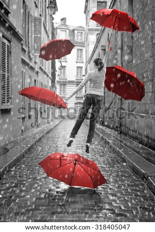 Girl with red umbrellas flying above-ground. Conceptual, surreal image. Black and white pictures with red elements.