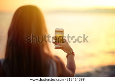 Tourist hand holding smart phone and taking photo of beautiful beach sunset
