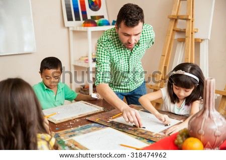 Young attractive male art teacher helping one of his students with her drawing during class #318474962