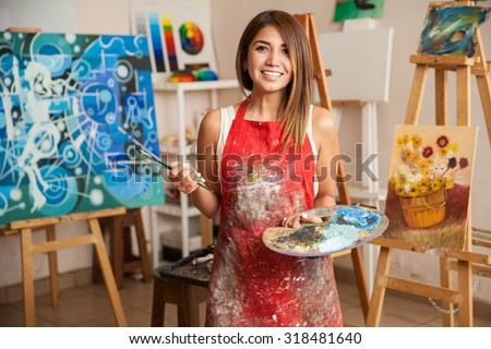 Portrait of a gorgeous female artist working on several art projects on her studio Royalty-Free Stock Photo #318481640