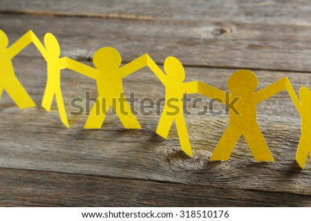 Paper people on the grey wooden background Royalty-Free Stock Photo #318510176