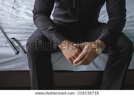 a man sitting on a bed in a black shirt #318538718