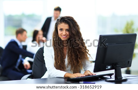 Happy young businesswoman looking behind and her colleagues working at office #318652919