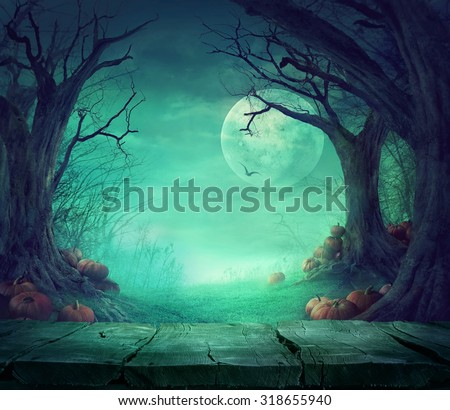 Halloween background. Spooky forest with dead trees and pumpkins and wooden table. Wood table. Halloween design with pumpkins Royalty-Free Stock Photo #318655940