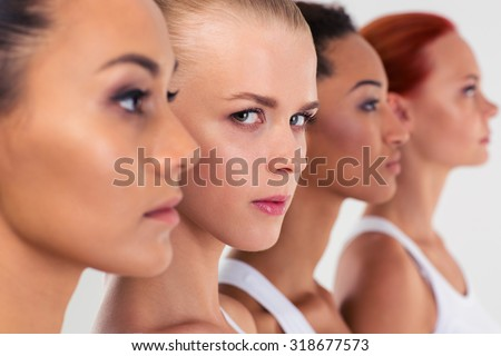 Portrait of a serious four woman standing in a row  #318677573