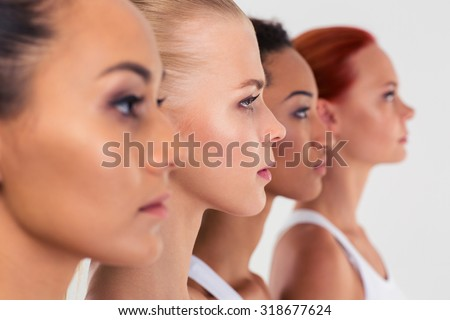 Portrait of a four women standing in a raw isolated on a white background #318677624