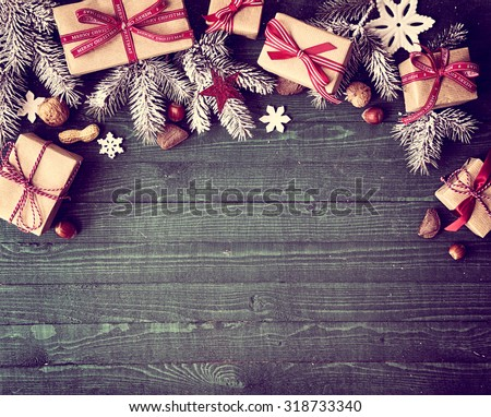Seasonal rustic Christmas border composed of decorative gifts, pine branches, nuts and snowflake ornaments over a wooden background with copyspace, overhead view #318733340