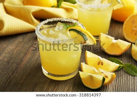 Glasses of lemon juice on wooden table, closeup #318814397
