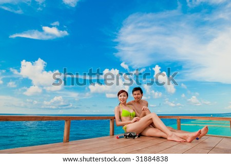 An attractive couple sitting on a wooden boat in the ocean #31884838