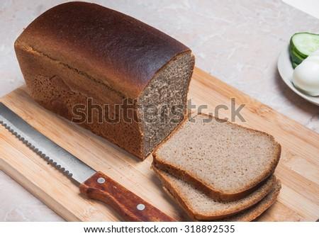 Sliced rye-wheat bread Darnytskyi and bread knife #318892535