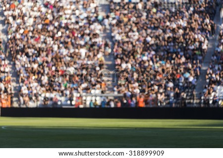 Blurred crowd of spectators on a stadium tribune at a sporting event Royalty-Free Stock Photo #318899909