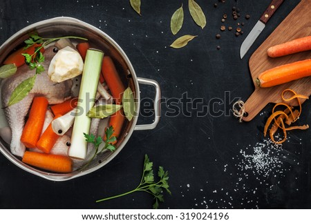 Preparing chicken stock (bouillon) with vegetables in a pot. Black chalkboard as background. Kitchen worktop scenery from above. Layout with free text space.