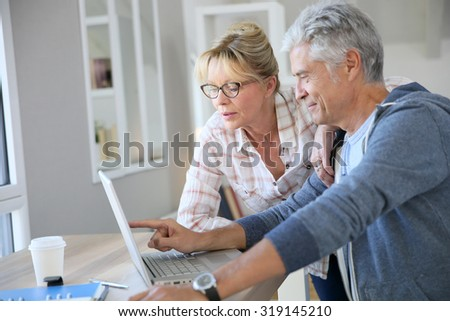 Senior couple at home checking expenses on internet #319145210