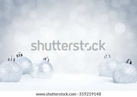 Silver Christmas baubles on snow with defocused silver and white lights in the background. Shallow depth of field. #319219148