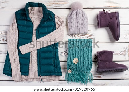 Knitwear on a wooden background. Fashionable female set of winter clothes.