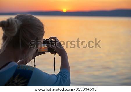 Girl taking photograph of sunset at Lake Balaton