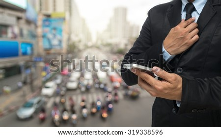 Businessman using the smart phone on abstract Blurred photo of traffic jam with rush hour #319338596
